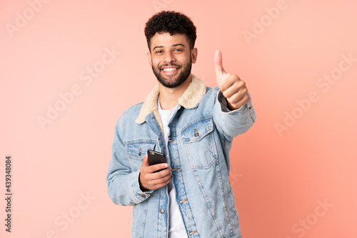Young Moroccan man using mobile phone isolated on pink background with thumbs up Fototapet