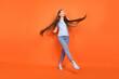 Leinwandbild Motiv Full size photo of impressed young lady dance wear blue t-shirt jeans isolated on orange color background