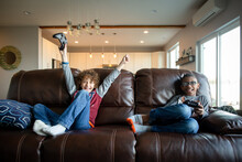 Boy Playing Video Game With Friend Raises Hands In Victory