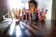 Child Plays With Decorated Popsicle Stick Dancers