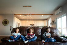 Siblings Sit On Leather Couch Holding Video Game Controllers