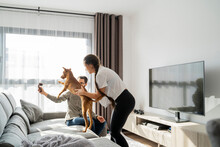 Young Couple Playing With Dog In Living Roon In Sofa