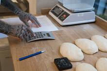 Close Up Of Baker Calculating Dough