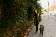 Woman Walking In The Sidewalk With Her Dog