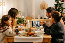 Family Doing A Videocall During Vegetarian Christmas Dinner In A Cozy Living Room