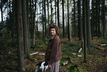 Woman In Casual Clothes Walking With Dog  In Forest