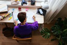 Focused Teen Studying At Desktop In Personal Room