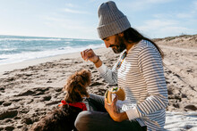 Long Hair Man Sharing Sandwich With His Little Dog