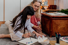Little Girl Painting Mandalas With Her Grandmother At Home