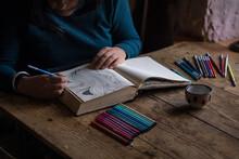 Female Artist Is Doodling  In Her Sketchbook