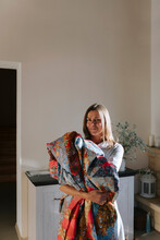 A Woman With A Patchwork Quilt In Her Hands.