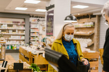 Senior Woman With Mask Paying With Credit Card At Store Counter