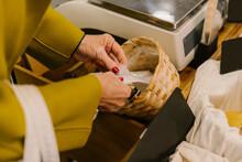 Detail Of Senior Woman Putting On Hygiene Gloves At Supermarket