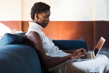 Calm Black Female Freelancer With Laptop On Sofa