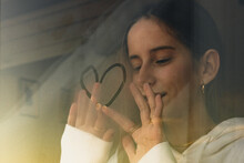 Teenager Girl Looking Trough Window Painting A Heart
