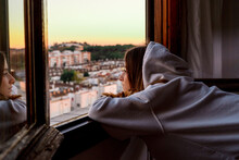 Teenager Girl Looking At The City From Her Home Window