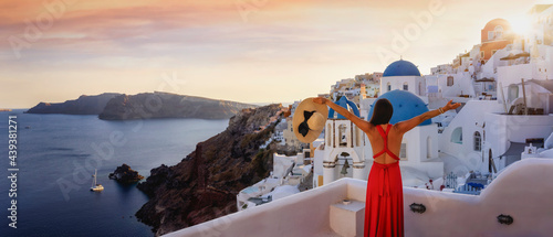 Fotografiet A tourist woman in a red dress enjoys the panoramic view of the village Oia and