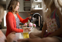 Woman Fills Vase From Faucet