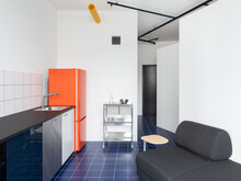 Kitchen With An Orange Fridge And Blue Tiles Floor
