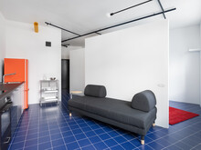 Kitchen With An Orange Fridge, Grey Couch And Red Carpet