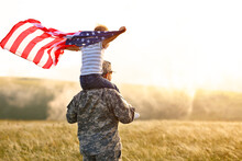 Excited Child Sitting With American Flag On Shoulders Of Father Reunited With Family