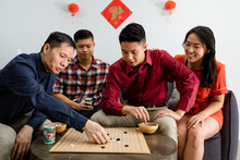 Asian Family Enjoys A Board Game During Chinese New Year