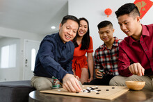 Chinese Family Enjoys A Board Game During Chinese New Year