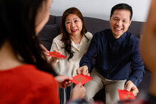 Parents Giving Children Red Envelopes On Chinese New Year