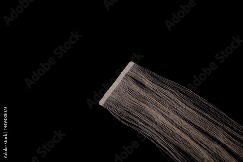 Fotografie, Obraz Fake blonde hair on sticky tape on black isolated background