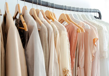 Stylish Womans Clothes Hanging On A Rack Natural Colors, Trending Concept,pastel Colors In White Room Modern Design Closeup