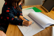 Little Girl Drawing Horse Rider On Notebook