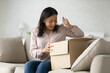 Happy excited parcel recipient unpacking received box, looking inside at surprising gift. Customer getting awaited purchase from internet store. Overjoyed woman opening package. Delivery concept