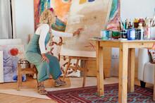 Senior Woman Examining A Canvas In Her Studio