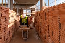 Builder Loading Cart With Bricks