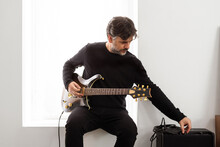 Man With Electric Guitar Tuning Amplifier