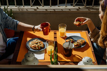 Couple Having Breakfast In Balcony During Sunny Day
