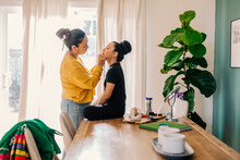 Woman Applying Makeup To A Girl Who Sits At Table