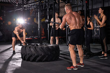 Muscular Men Having Sports Training For Endurance, Man Hits Hammer. Concept Workout. Fitness Competition With Large And Heavy Tire Hits Hammer.