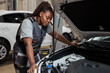 Tired african auto mechanic woman misunderstanding what is wrong with car, looking inside of hood, side view portrait. Young female in auto service. copy space