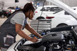 Young afro american woman mechanic holding clipboard checklist at service center repair, side view on confident serious black female at work, thinking. in auto service