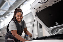 Black Female Car Mechanic Holding Wrench Checking Up On The Car Engine, For Repair And Checkup, Wearing Overall, Repairing Auto Hood. Side View Portrait. Copy Space