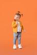 Leinwandbild Motiv Cute little girl eating lollipop on color background