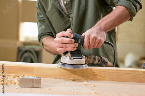 Cropped male carpenter carefully smoothing wooden material with electrical sander, concentrated on work, enjoy woodworking, side view portrait of man making furniture Fototapet