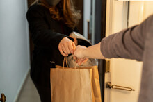 Woman Delivering Take Away Food To Man At Home