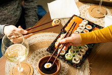 Couple Having Sushi On Coffe Table In Living Room
