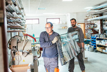 Male Workers With Aluminum Window Glass In Workshop