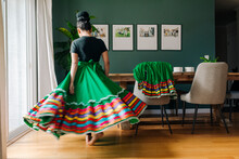 Back View Tween Girl Trying On Her Traditional Mexican Folkloric Skirt At Home