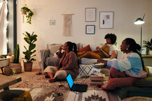 Black Women Watching Film Together In Evening