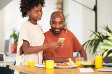 Black Couple Embracing And Reading Message On Smartphone.