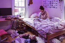 College Student Studying In Messy Room